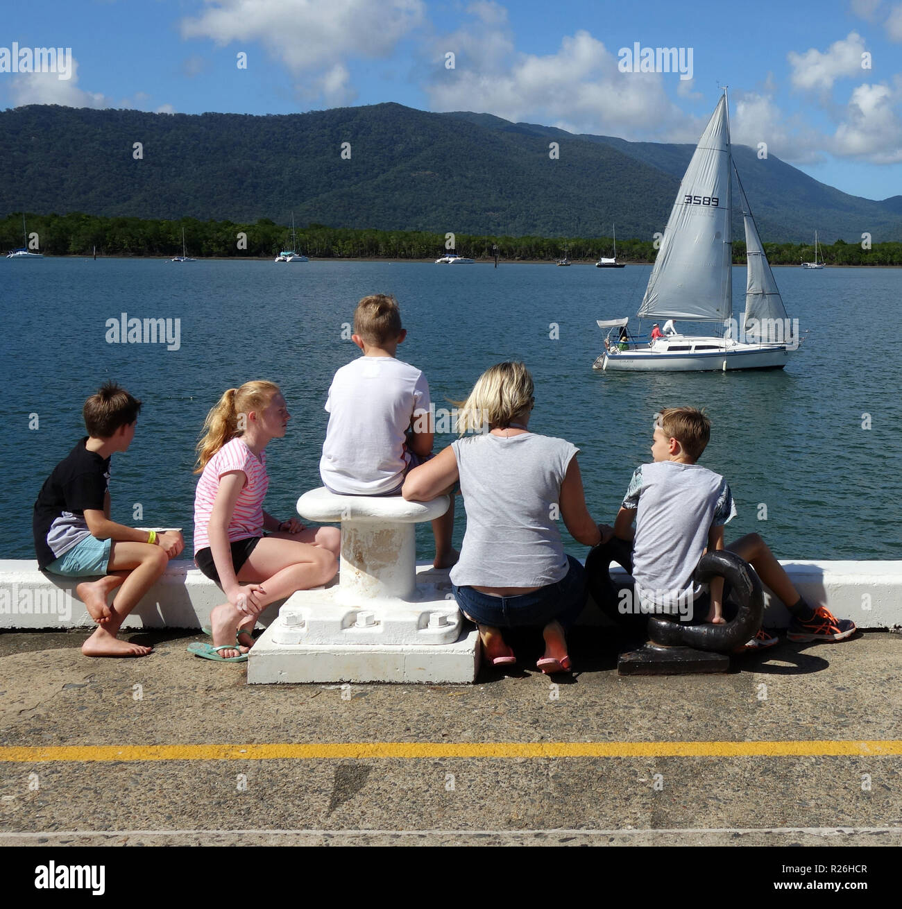 Family watching passing sailboat on Trinity Inlet, Cairns, Queensland, Australia. No MR or PR - Stock Image