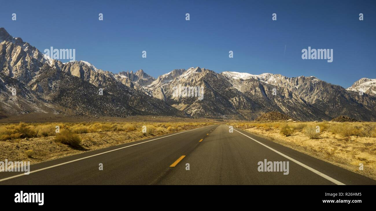 Driving Iconic California State Highway 395 in Owens Valley on Eastern Flanks of Sierra Nevada Mountains with Distant Mount Whitney on Horizon - Stock Image