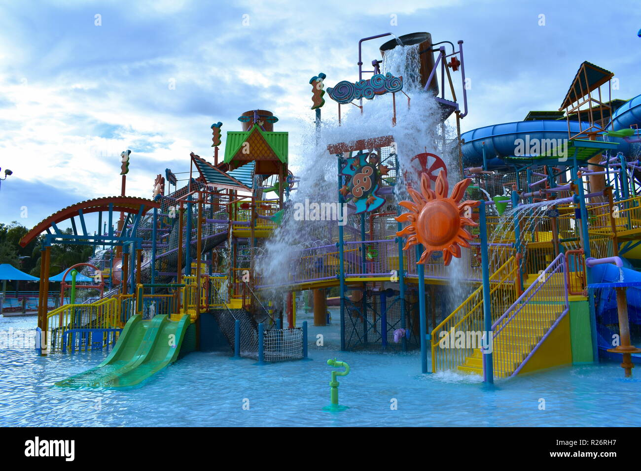 Orlando, Florida. October 25, 2018. Colorful  Attraction with splashing water in lightblue pool on cloudy sky background at Aquatica Water Park - Stock Image