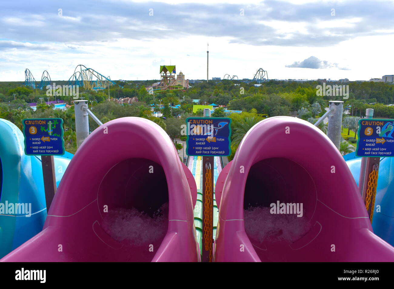 Orlando, Florida. October 26, 2018. Colorful slides water ride attraction with top view of Seaworld and Aquatica Parks on cloudy sky background. - Stock Image