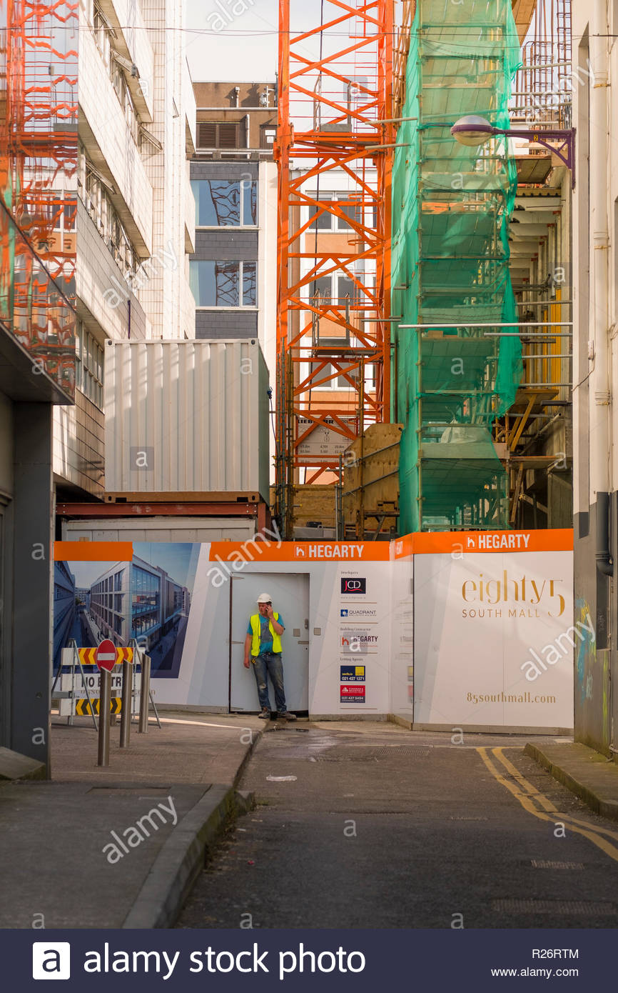 Man wearing hardhat and high visibility vest standing at entrance to construction site talking on a cellular phone, Smith Street, Centre, Cork, County - Stock Image