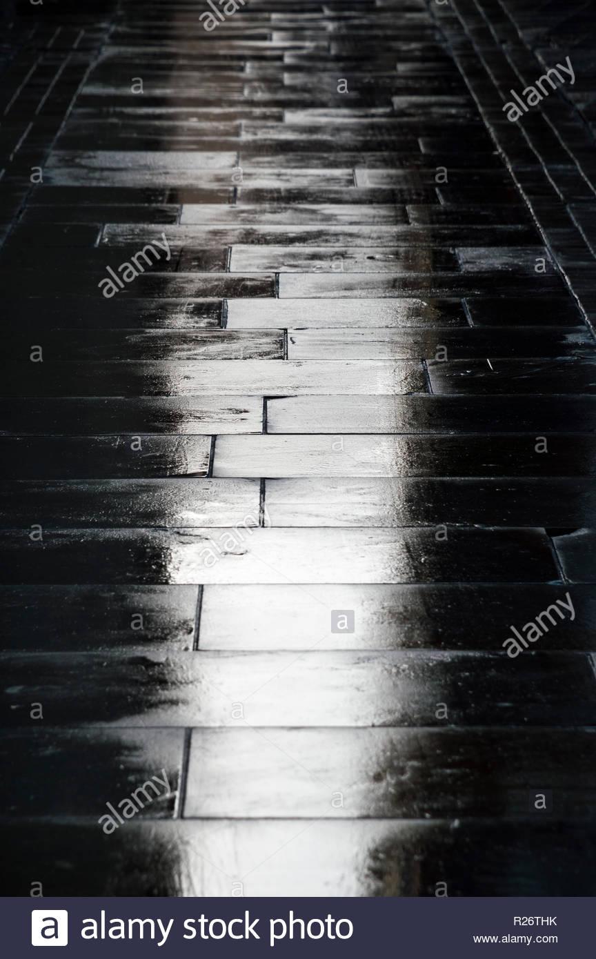 Looking down at wet paving in Salisbury, Wiltshire, England, UK - Stock Image