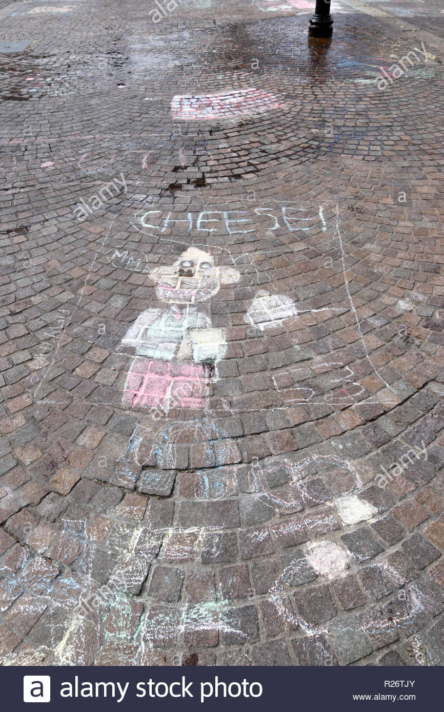 Looking down on the muted colours of a chalk child's drawing on paving in Newbury, Berkshire, England, UK - Stock Image