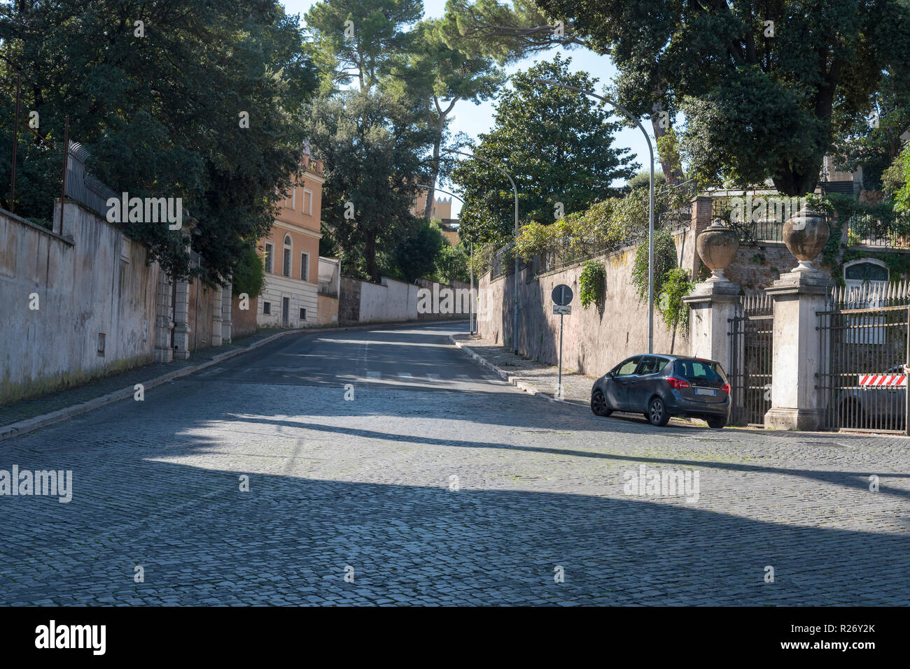 Road, home car in Rome on a summer day. The road from the pavers goes up the  hill.