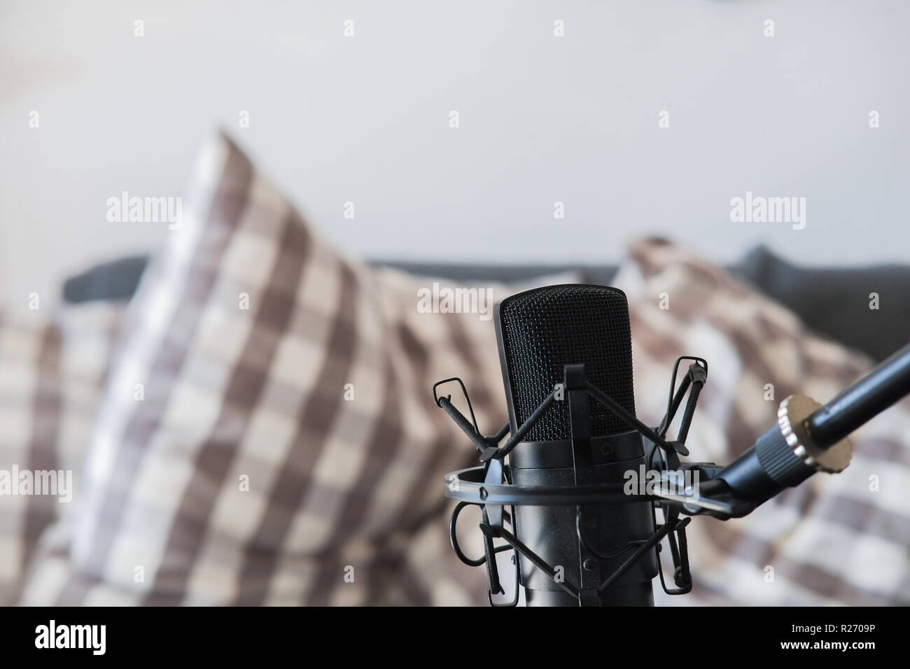 Condenser microphone on microphone stand with sofa in background Stock Photo