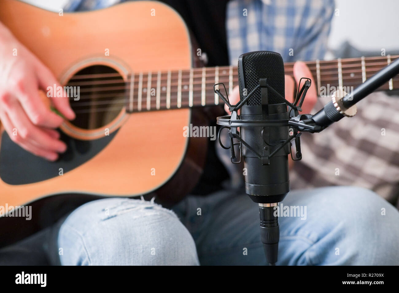 Young male recording his acoustic guitar with condenser microphone Stock Photo