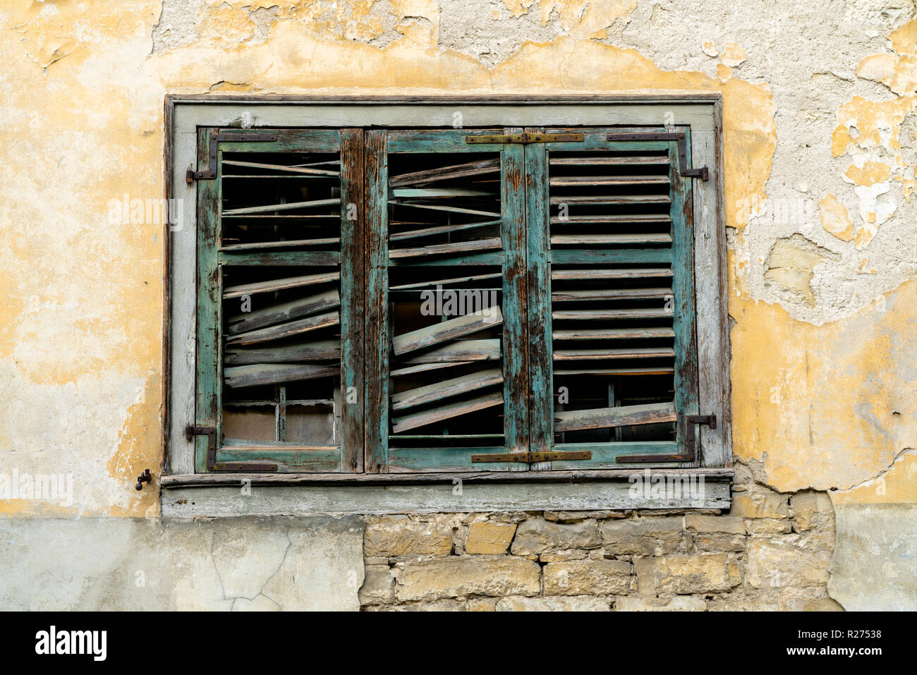 old broken window shutters on a dilapidated and run down house front with chipped paint and plaster - Stock Image