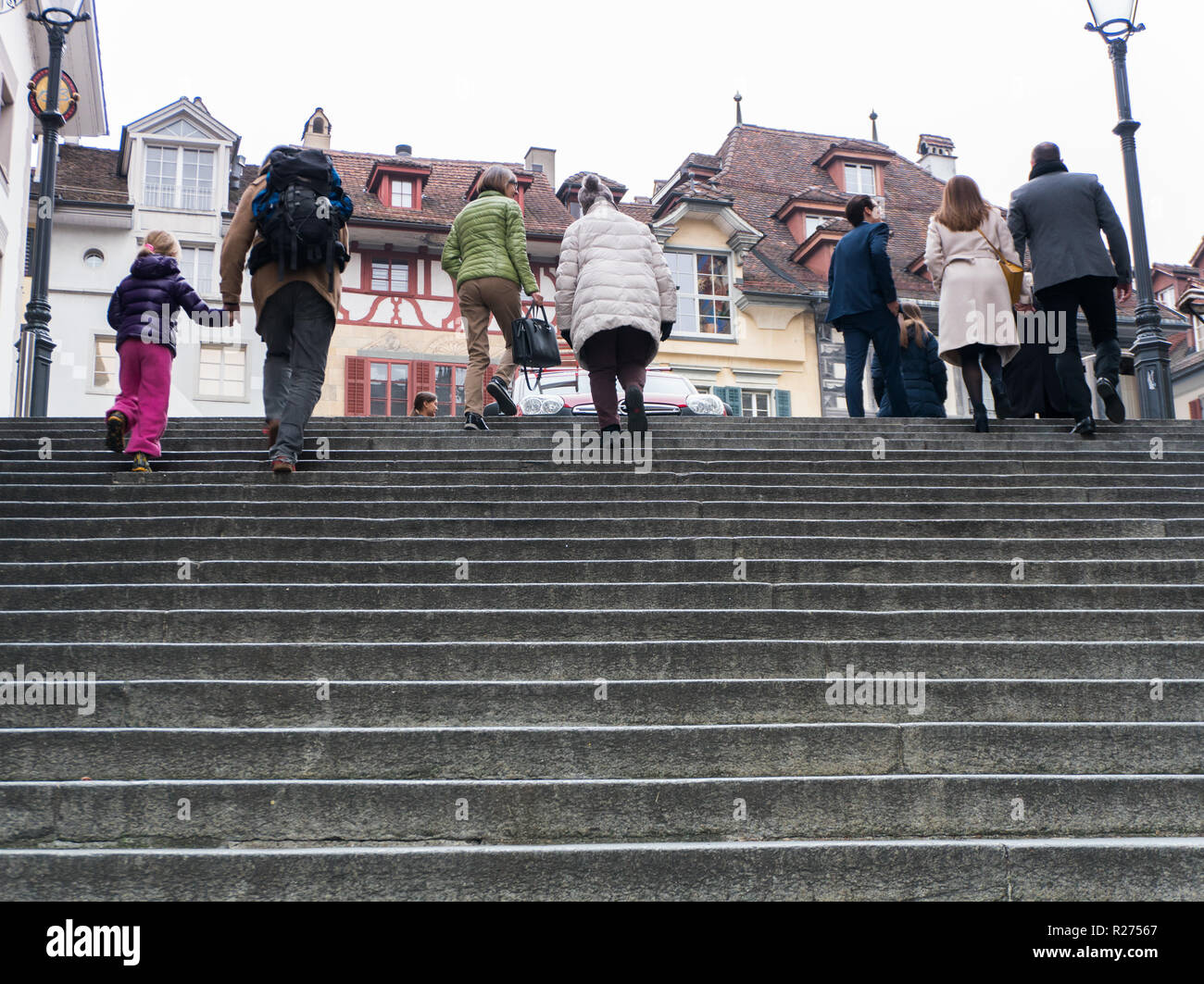 Lucerne, LU / Switzerland - November 9, 2018: many people of different age and gender rushing up and down old stone stairs in the historic city of Luc - Stock Image