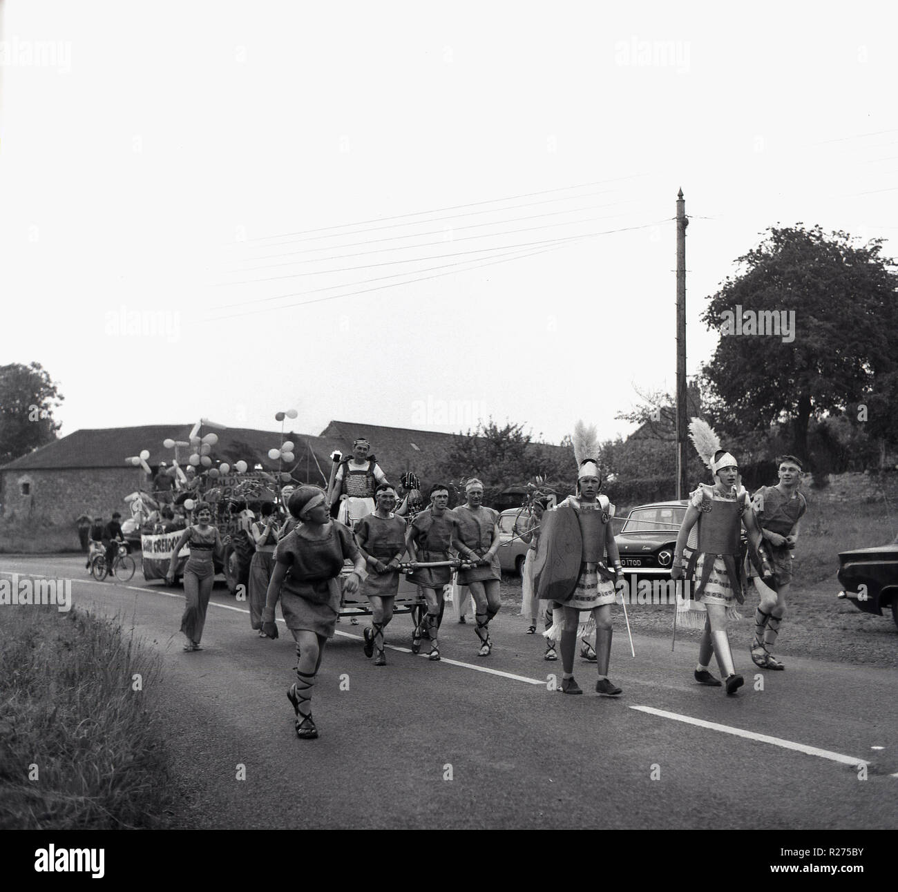 1967, historical, English village carnival, people dressed up as Roman centurions walking along a country road as they take part in a local village parade, Oxfordshire, England, UK. - Stock Image