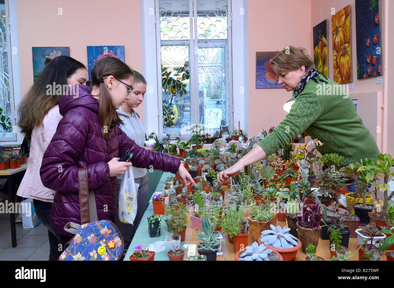 At the flower shop. Seller keeping a pot with cactus and talking to a  customer. Kiev, Ukraine. October 12, 2018 Stock Photo