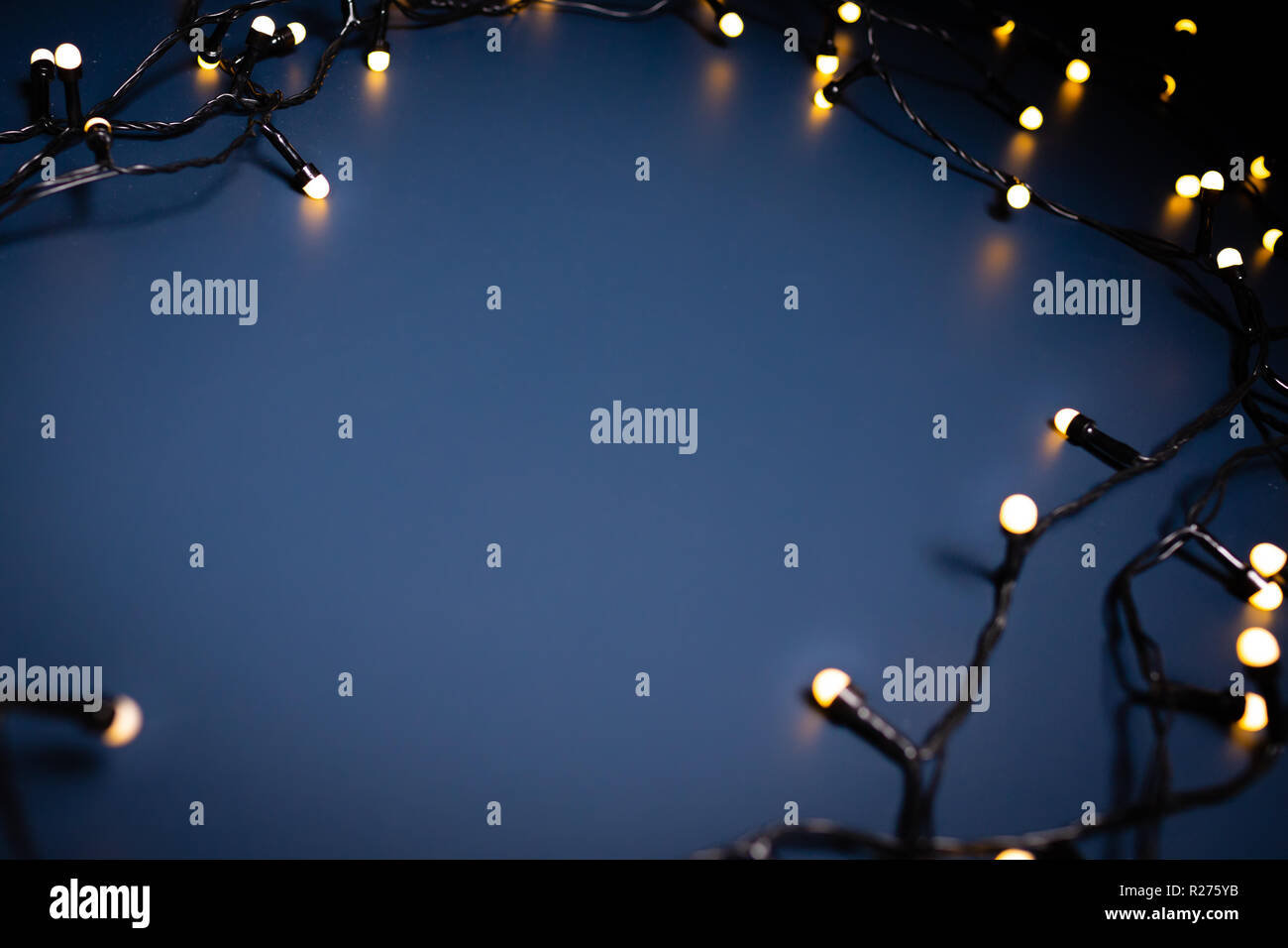Blue background surrounded by decorative lights. Christmas theme. - Stock Image