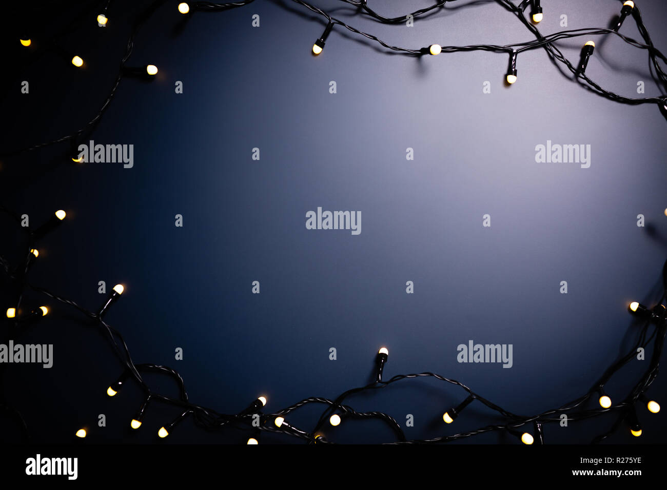 Blue background surrounded by decorative lights. - Stock Image
