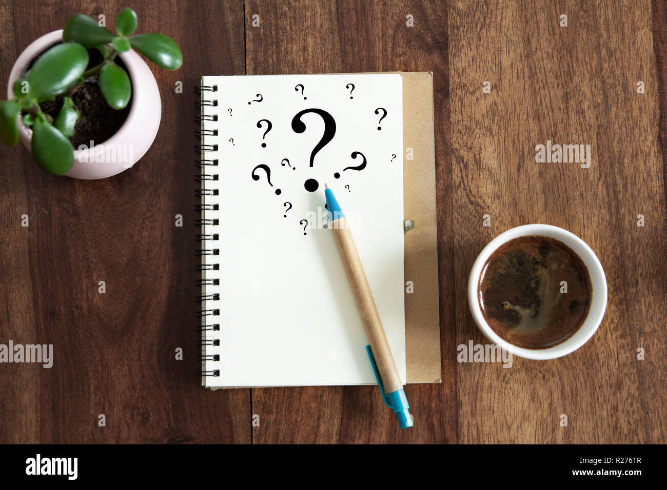 question mark symbols in notebook laying on office desk. flat lay view. - Stock Image