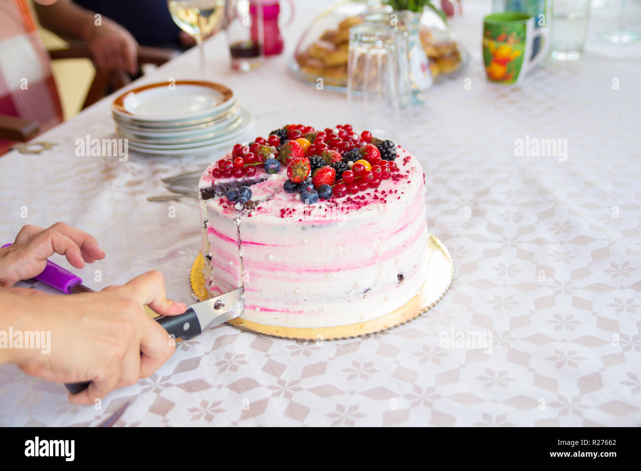Hand With Knife Slicing Birthday Cake