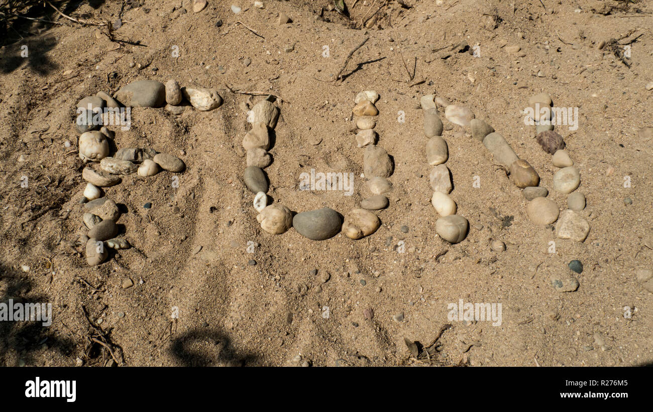 Das englische Wort für Spaß, Fun mit Kiesel Steinen in den Sand gelegt - Stock Image