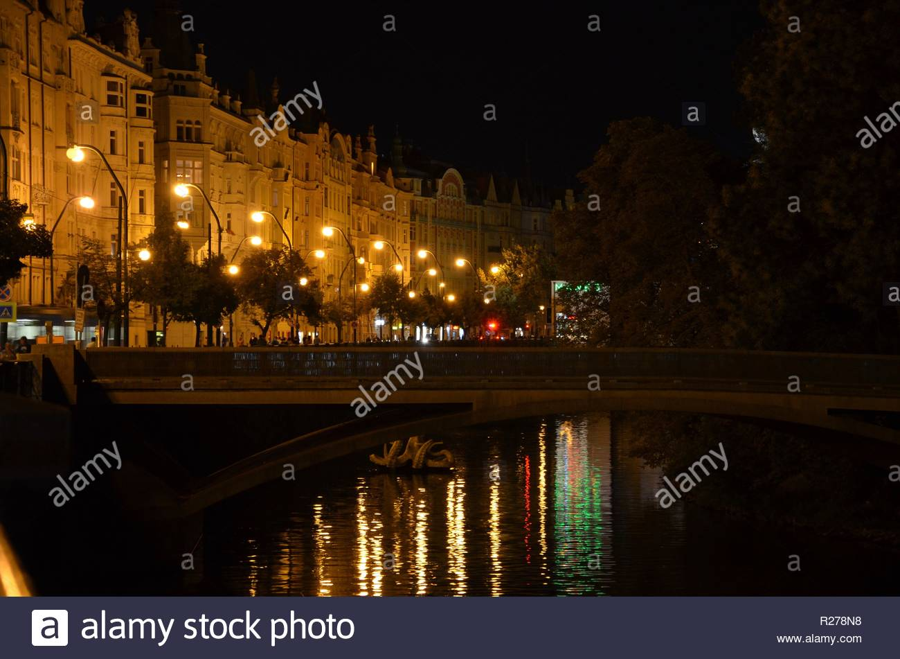 Prague at night, illuminated street, reflections of the lights on water surface of river Moldau - Stock Image