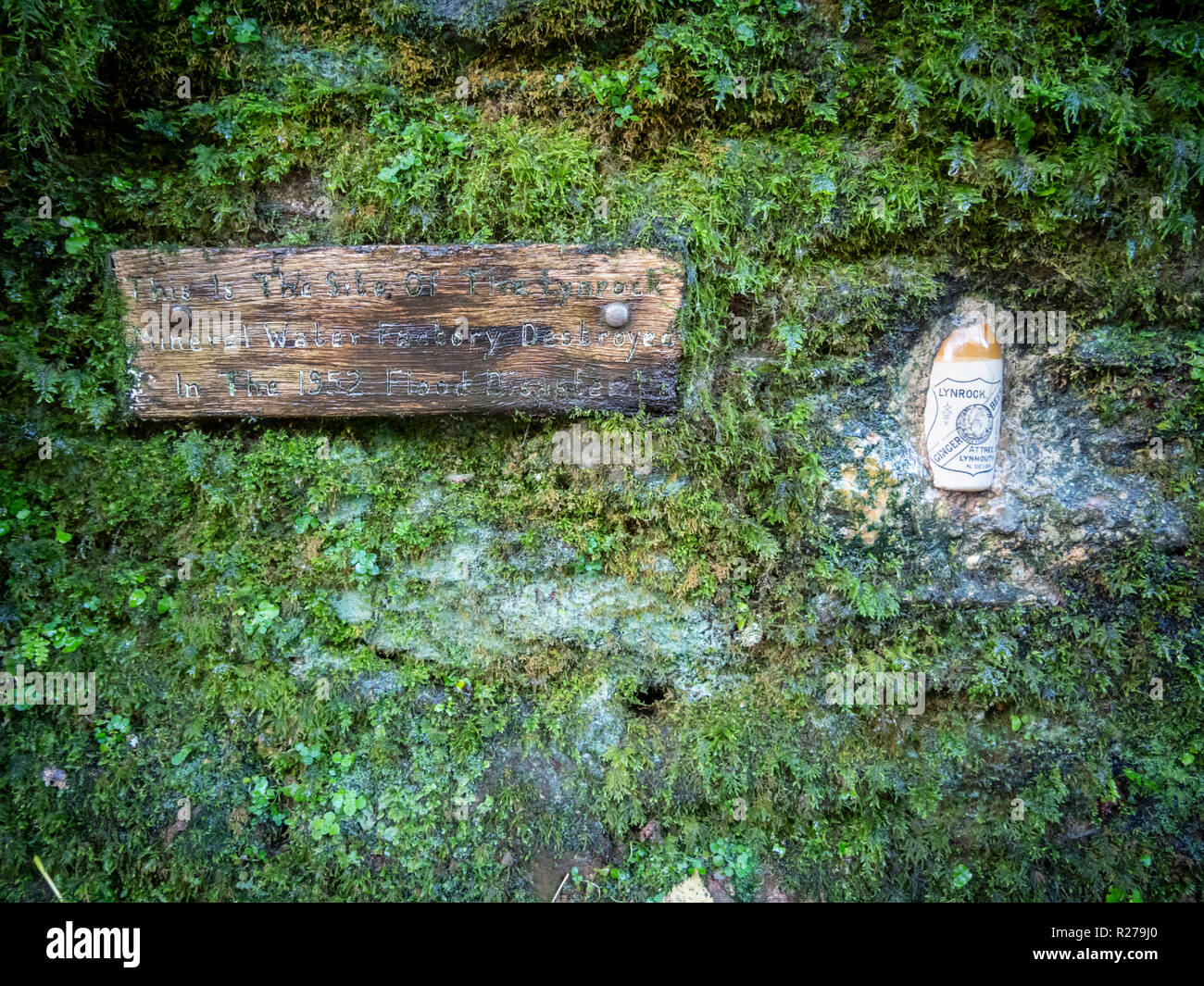 An old Lynrock ginger beer bottle set in a wall in the west Lyn River Valley  at Lynmouth, Exmoor, Devon UK on the site of an old mineral water factor - Stock Image