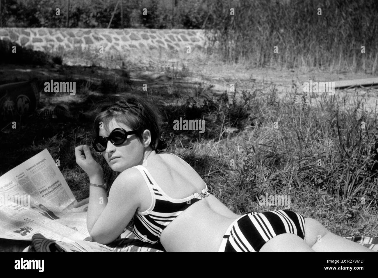 young female in a biking wearing sunglasses reading a newspaper 1970s hungary - Stock Image