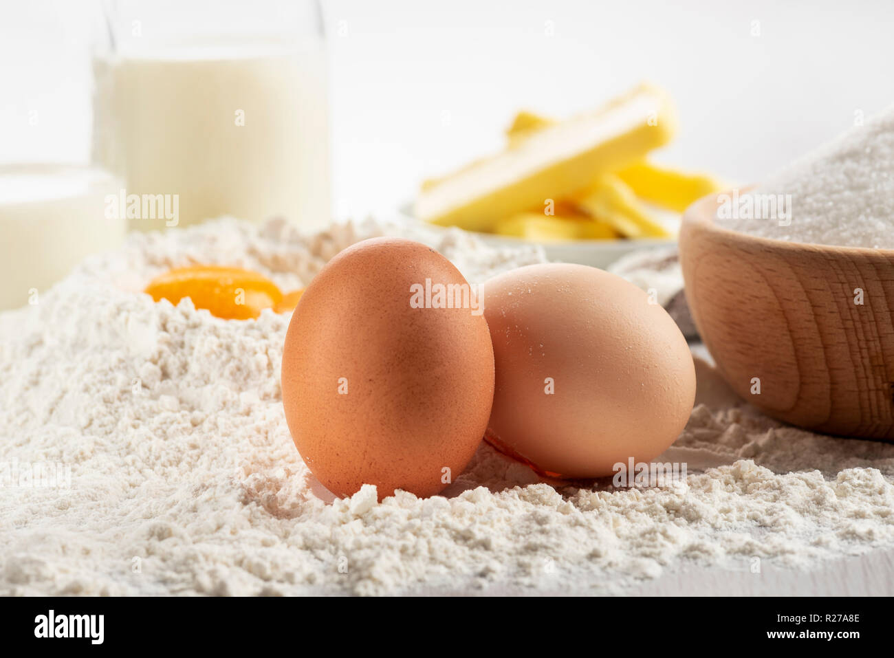 Ingredients for dough and pastry on wooden table, close up on eggs. - Stock Image