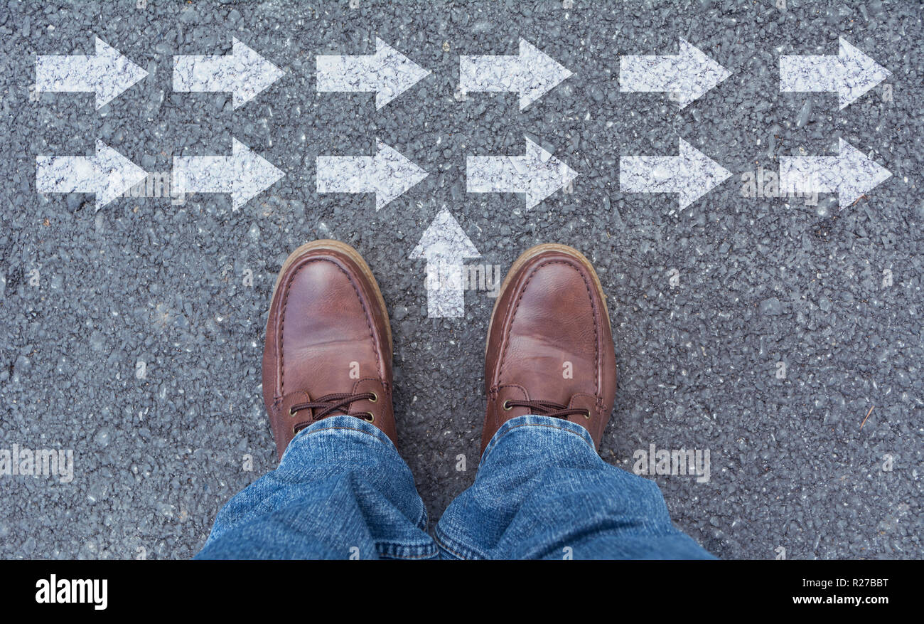 Top view of man wearing shoes choosing a way marked with arrows. Chooses the right path concept. - Stock Image