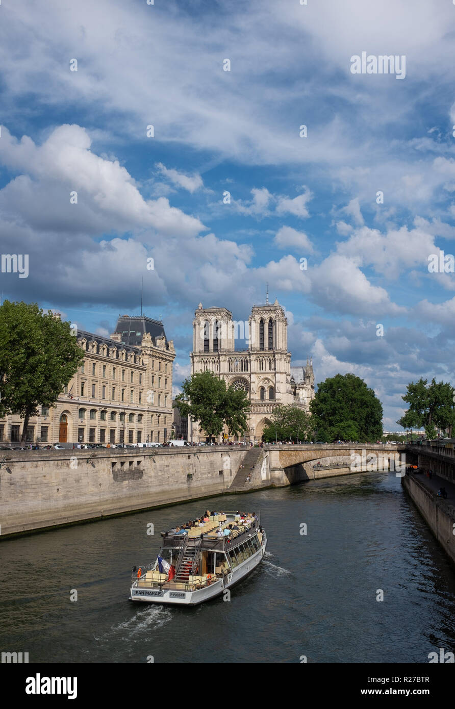 Sightseeing boat moving on river Seine near Notre-Dame de Paris cathedral, Paris, France - Stock Image