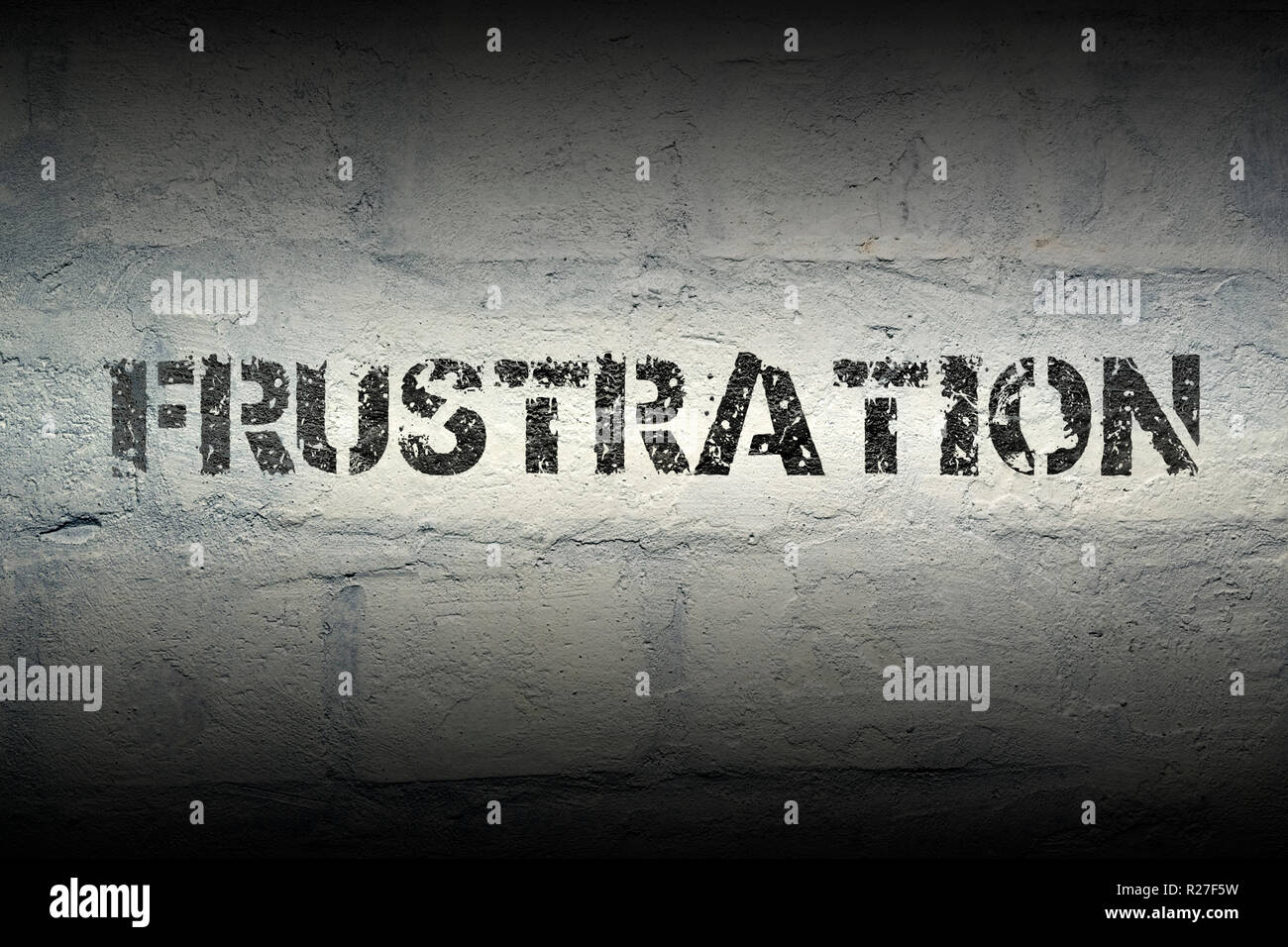 frustration stencil print on the grunge white brick wall - Stock Image