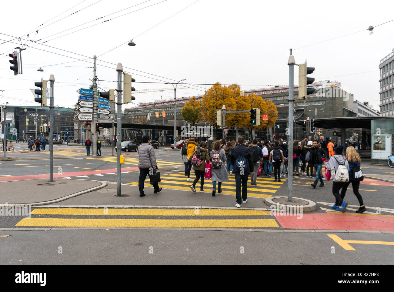 Lucerne, LU / Switzerland - November 9, 2018: many pedestrians crowd an intersection island at a busy road and crosswalk during rush hour in Lucerne i - Stock Image