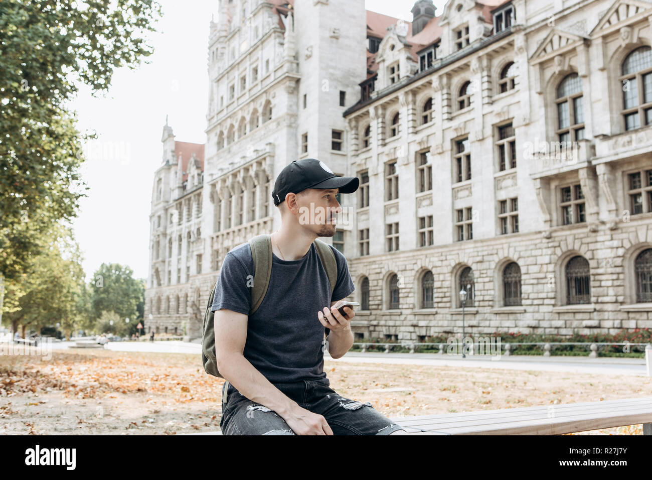 A tourist man or boy with a backpack or a student in Leipzig in Germany uses a mobile phone to view a map or call or for another. - Stock Image