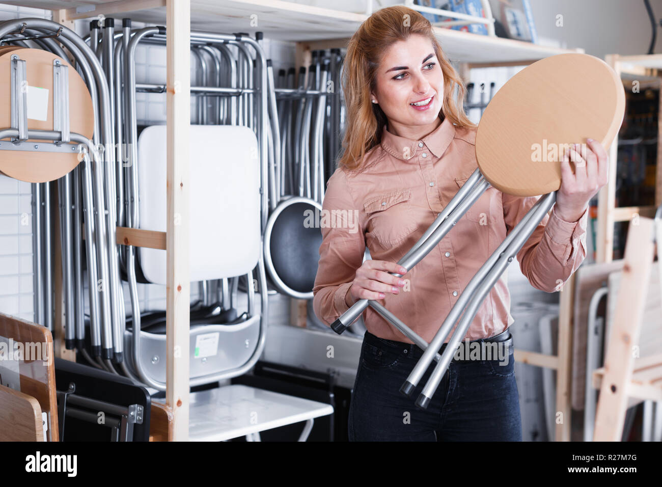 Glad woman looking for new stylish tabouret for apartment in furniture salon - Stock Image