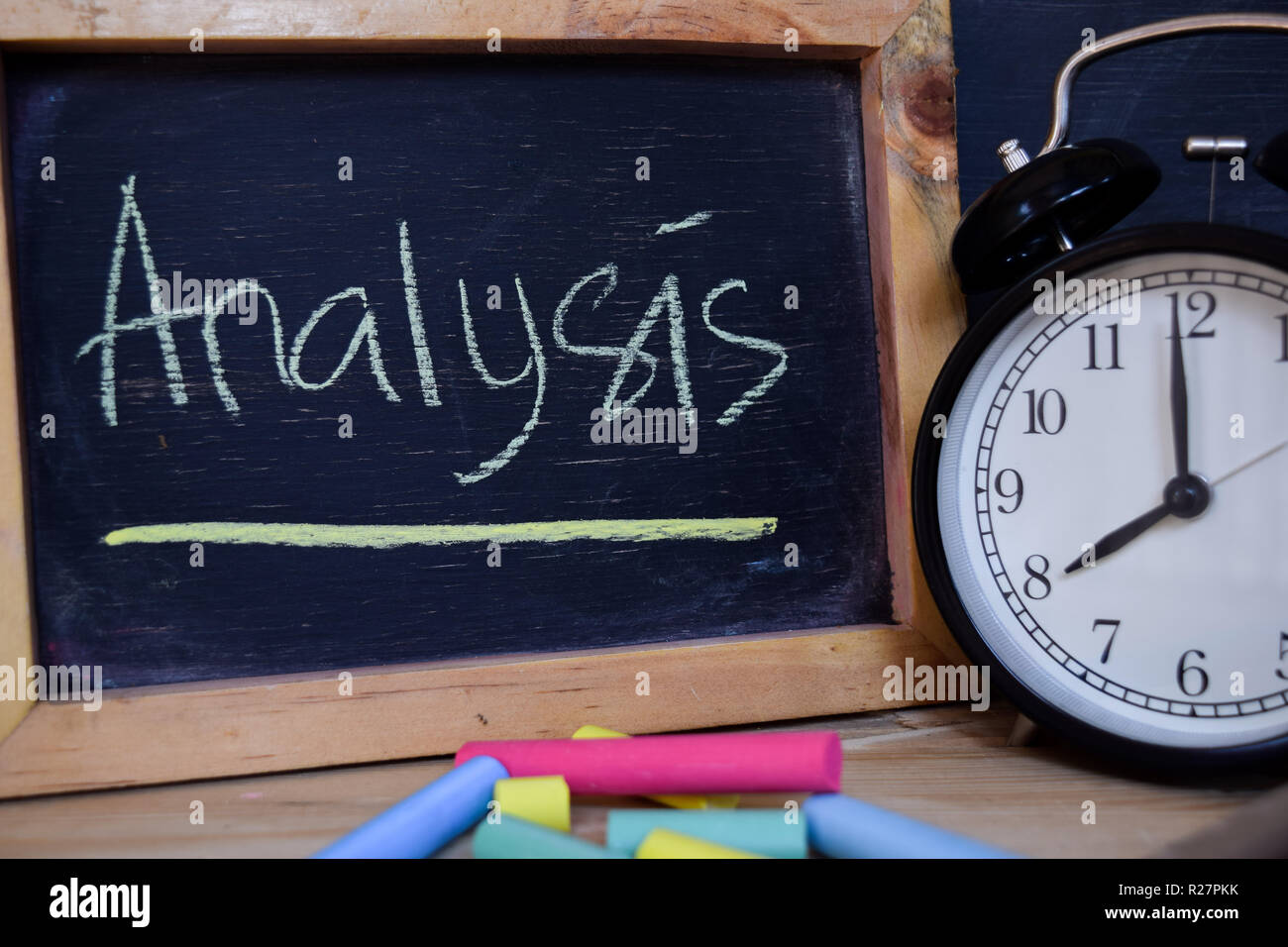 Analysis. Back to school concept. Alarm clock on wooden with blackboard on background Stock Photo