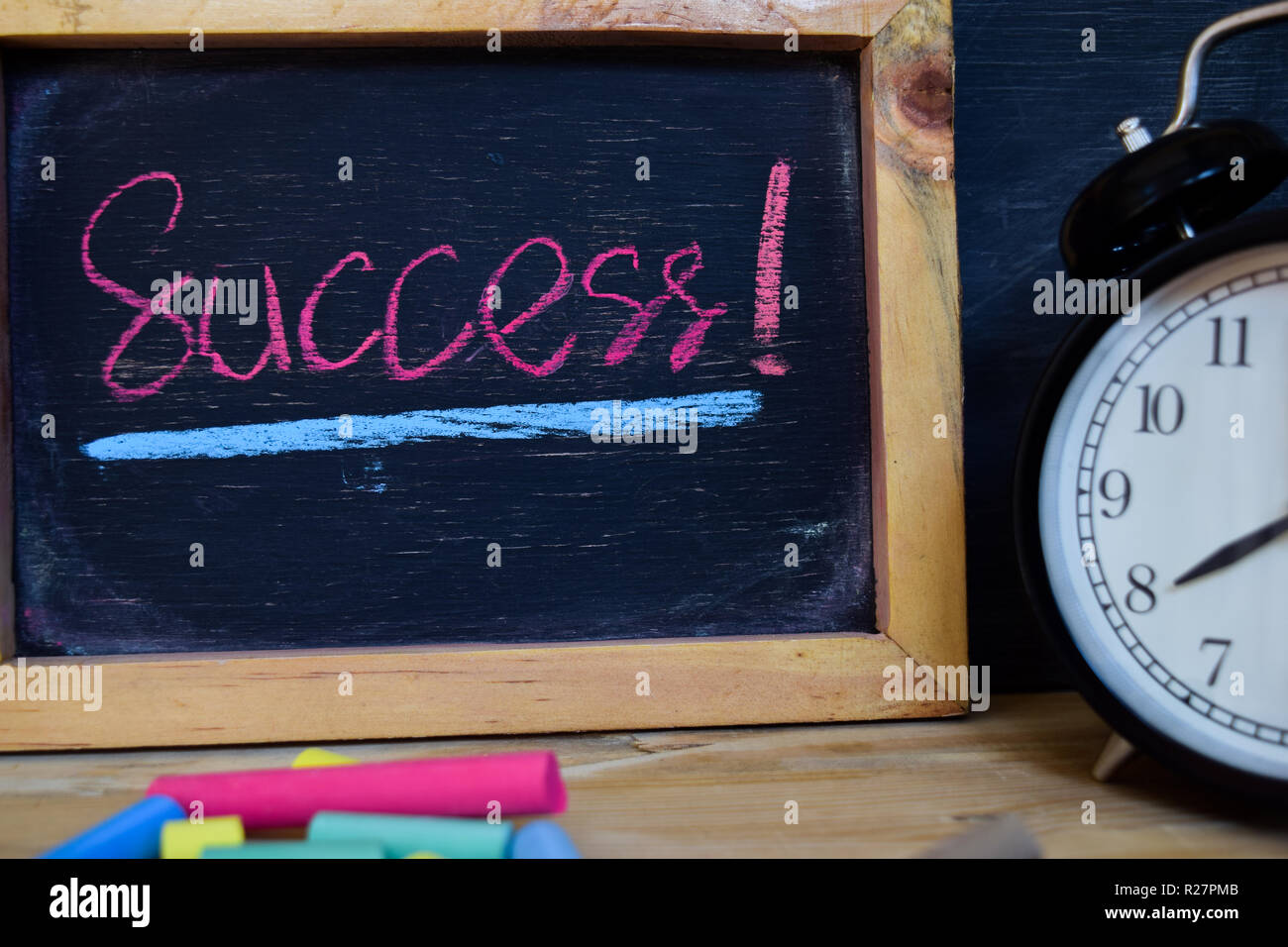 Success. Back to school concept. Alarm clock on wooden with blackboard on background Stock Photo