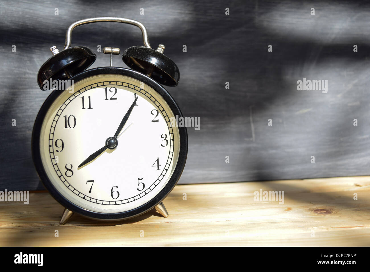 8 am/pm Back to school concept. Alarm clock on wooden with blackboard on background - Stock Image
