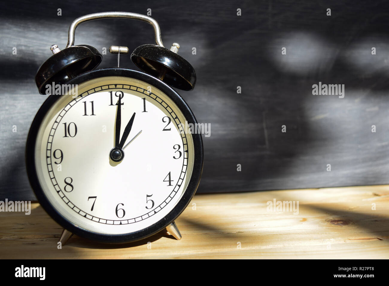 1 am/pm Back to school concept. Alarm clock on wooden with blackboard on background - Stock Image