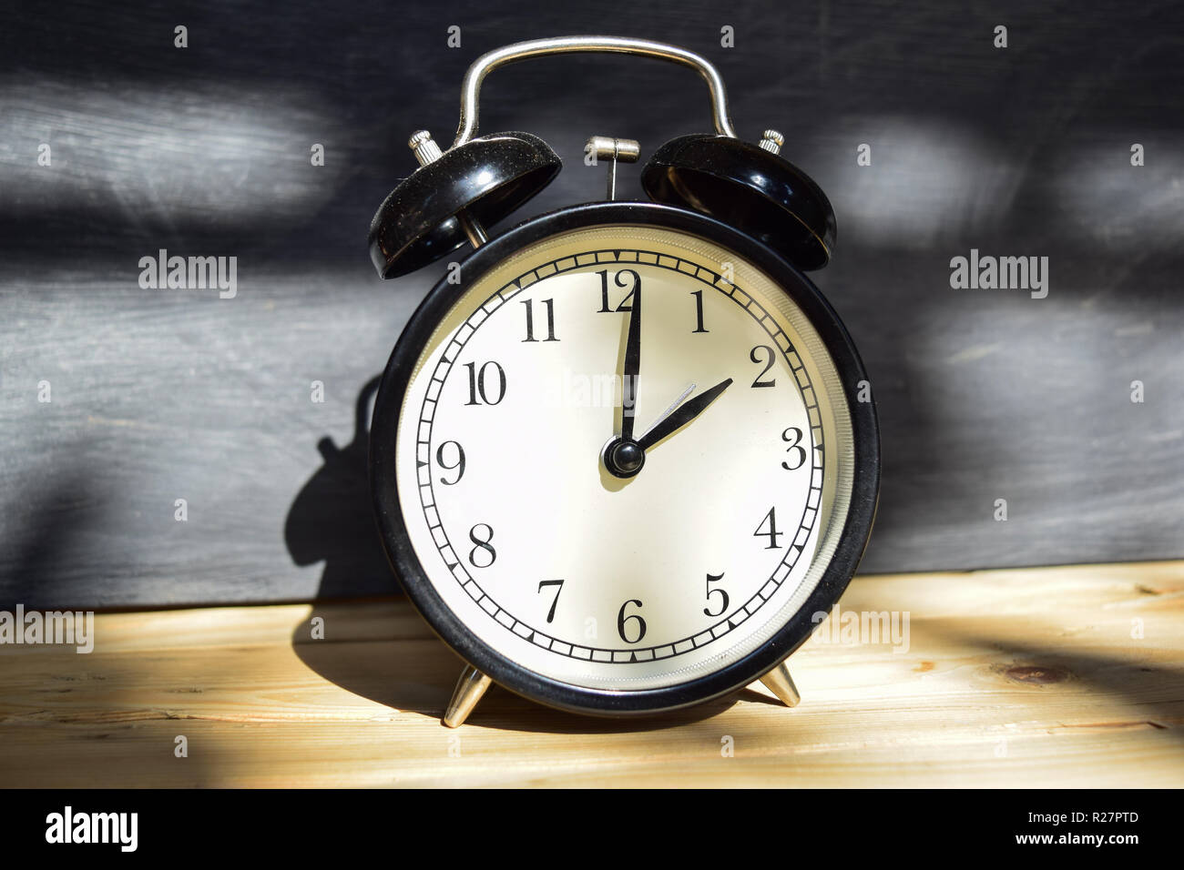 2 am/pm Back to school concept. Alarm clock on wooden with blackboard on background - Stock Image