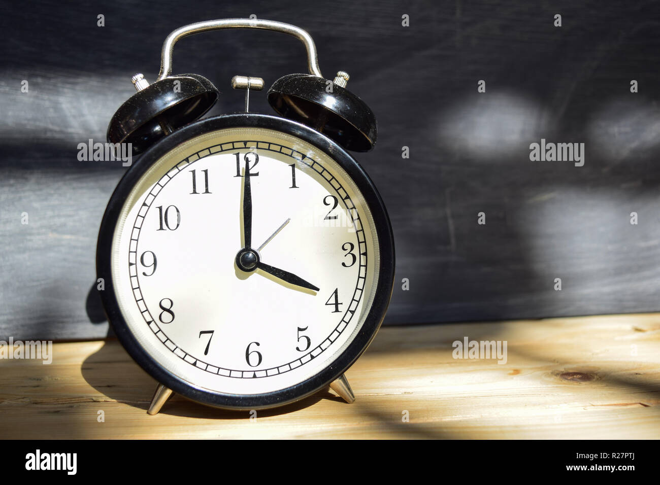 4 am/pm Back to school concept. Alarm clock on wooden with blackboard on background - Stock Image