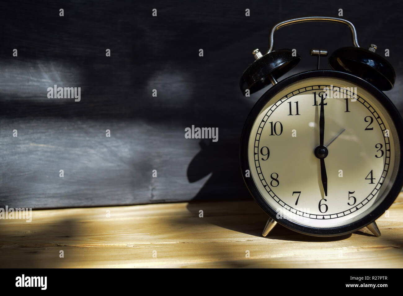 6 am/pm Back to school concept. Alarm clock on wooden with blackboard on background - Stock Image