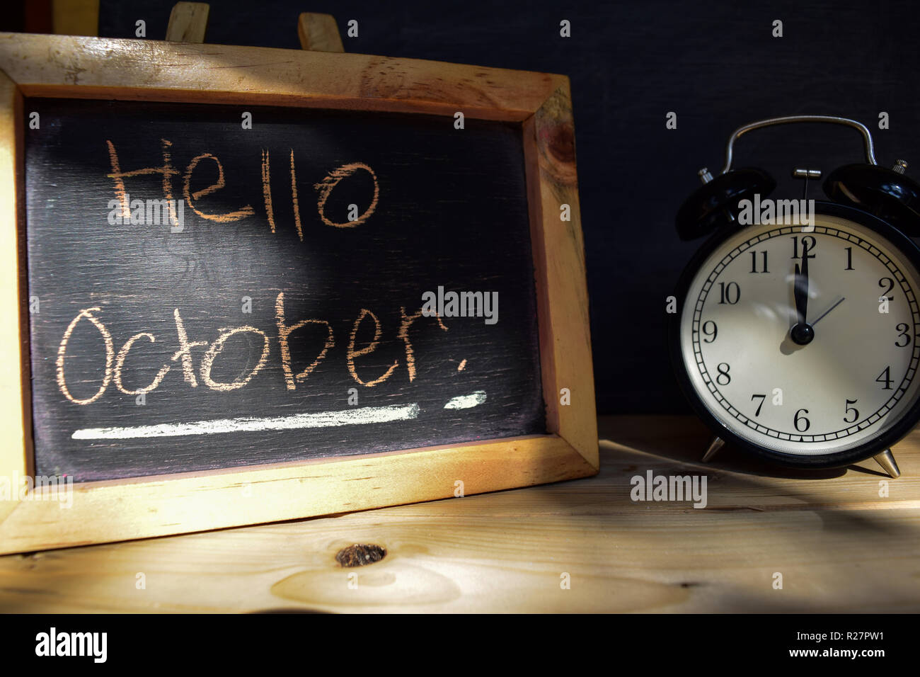 Hello october. Back to school concept. Alarm clock on wooden with blackboard on background - Stock Image