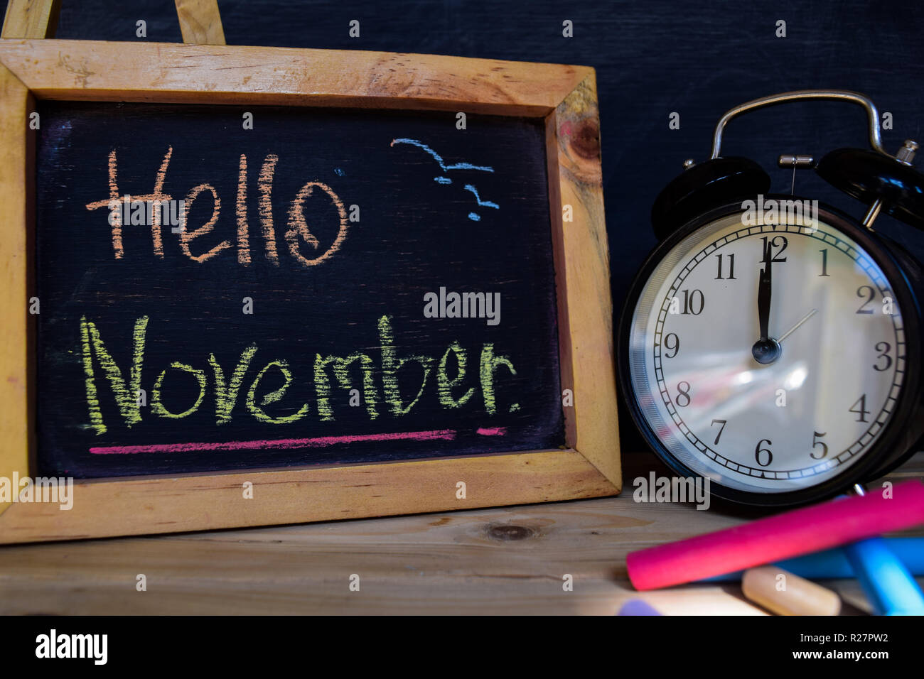 Hello november. Back to school concept. Alarm clock on wooden with blackboard on background - Stock Image