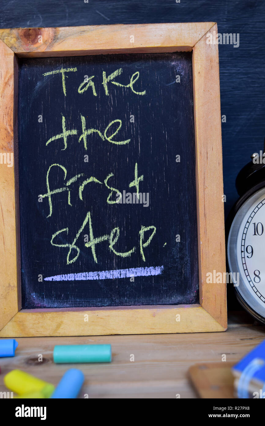 Take the first step. Back to school concept. Alarm clock on wooden with blackboard on background - Stock Image