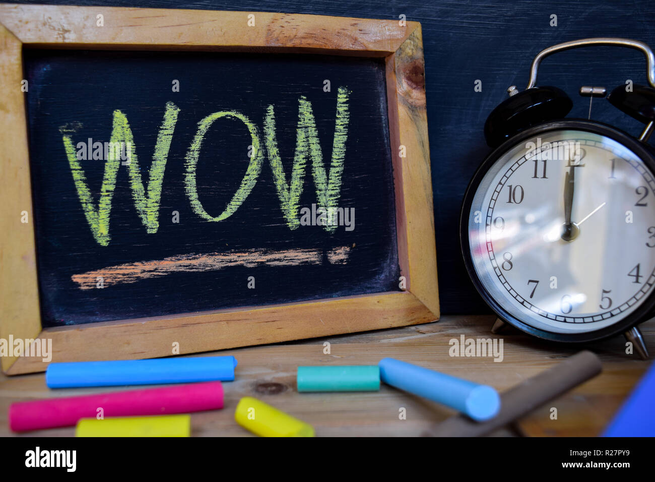 Wow. Back to school concept. Alarm clock on wooden with blackboard on background - Stock Image