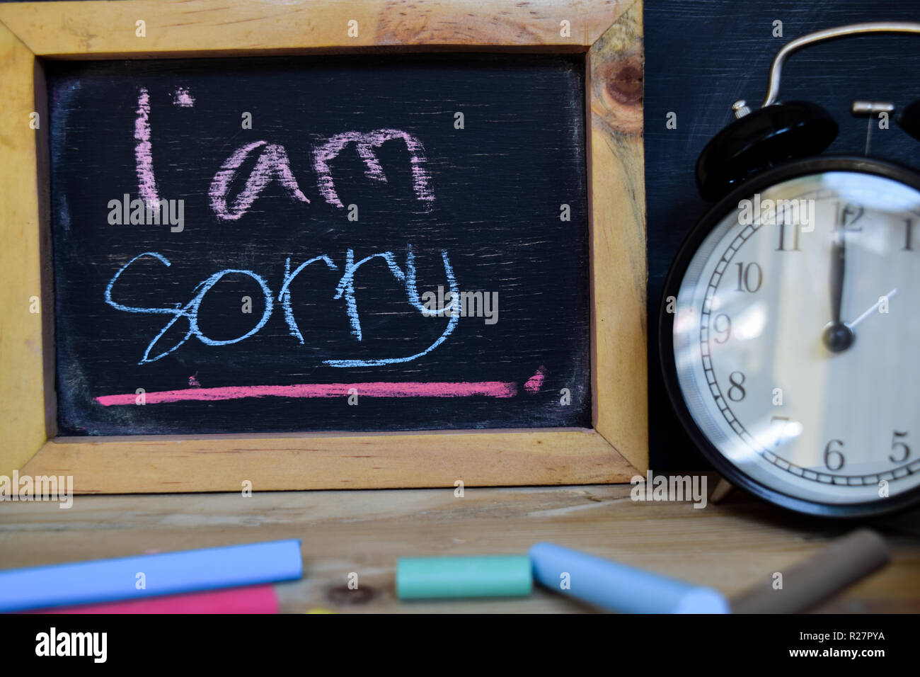 I am sorry. Back to school concept. Alarm clock on wooden with blackboard on background - Stock Image