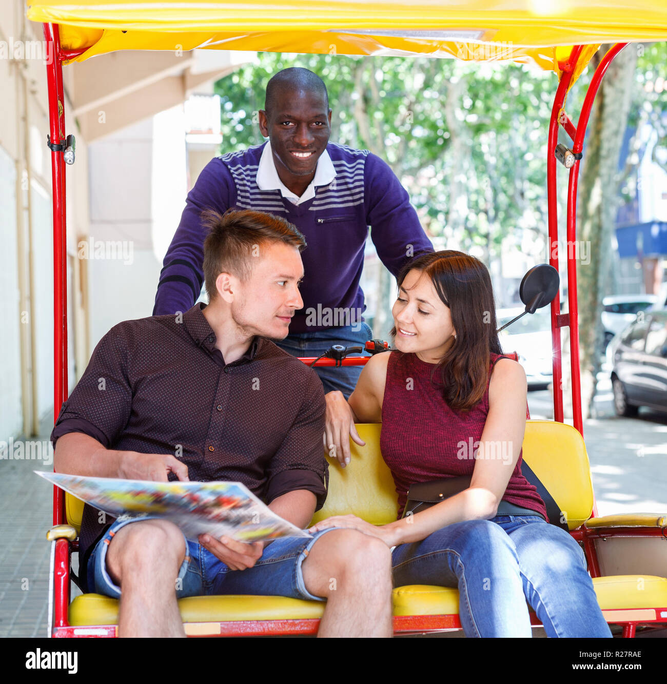 Young loving happy cheerful positive couple enjoying tour of city on trishaw with affable African American driver - Stock Image