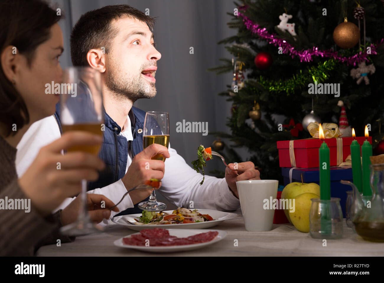 Family couple having christmas dinner with champagne and watching tv - Stock Image