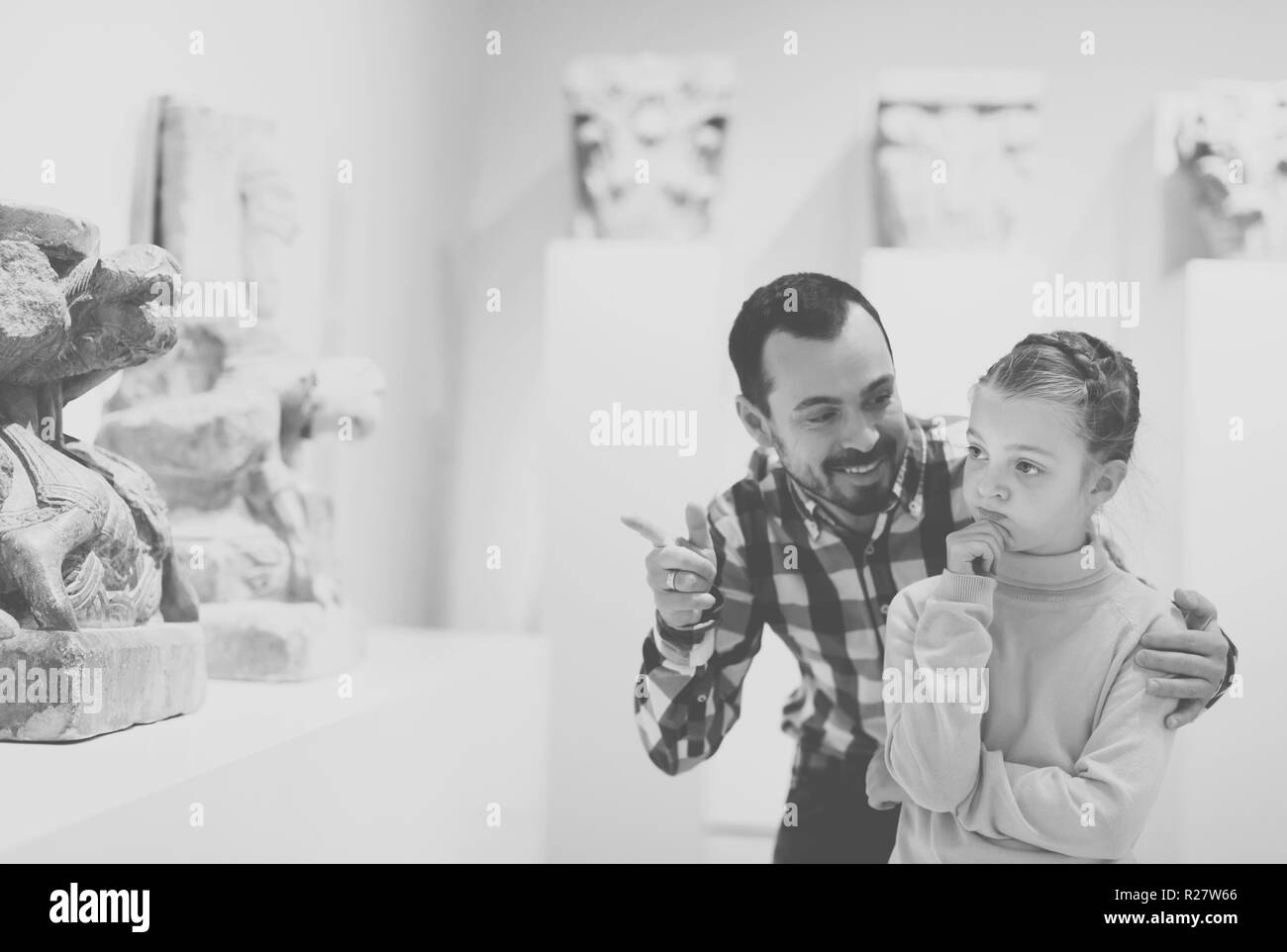 Smiling man and small daughter looking ancient statues in museum - Stock Image