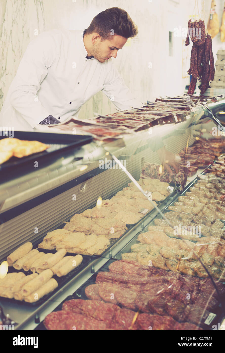 Young shop assistant in grocery shop showing fresh meat - Stock Image
