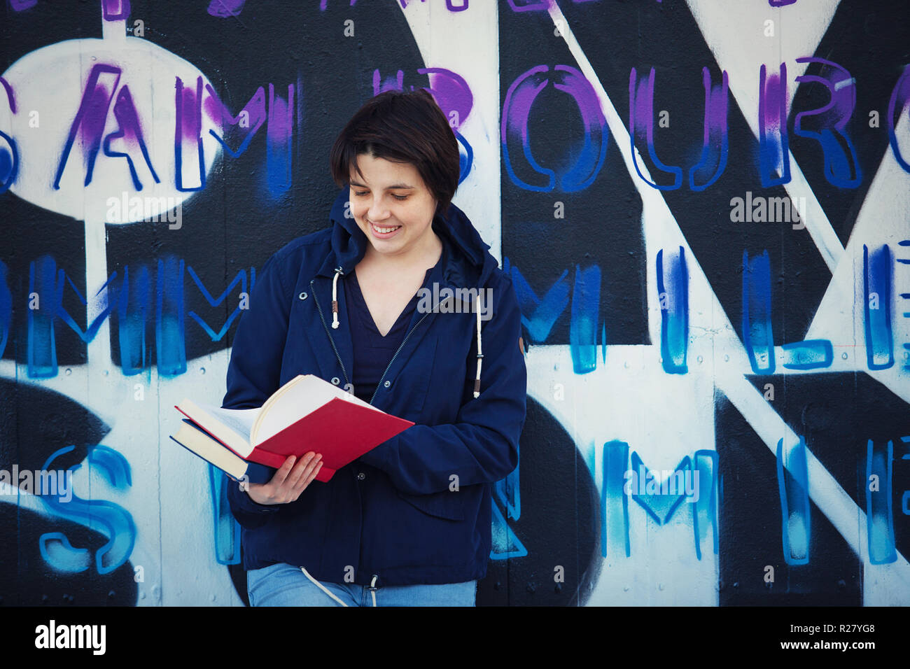 Casual happy woman student reading book, outdoors lifestyle portrait leaning back on graffiti wall background. Education concept, street art. Stock Photo