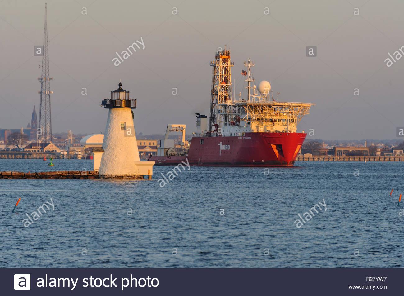 New Bedford, Massachusetts, USA - January 19, 2018: Geotechnical drill ship Fugro Explorer passing Palmer's Island lighthouse during early morning dep - Stock Image