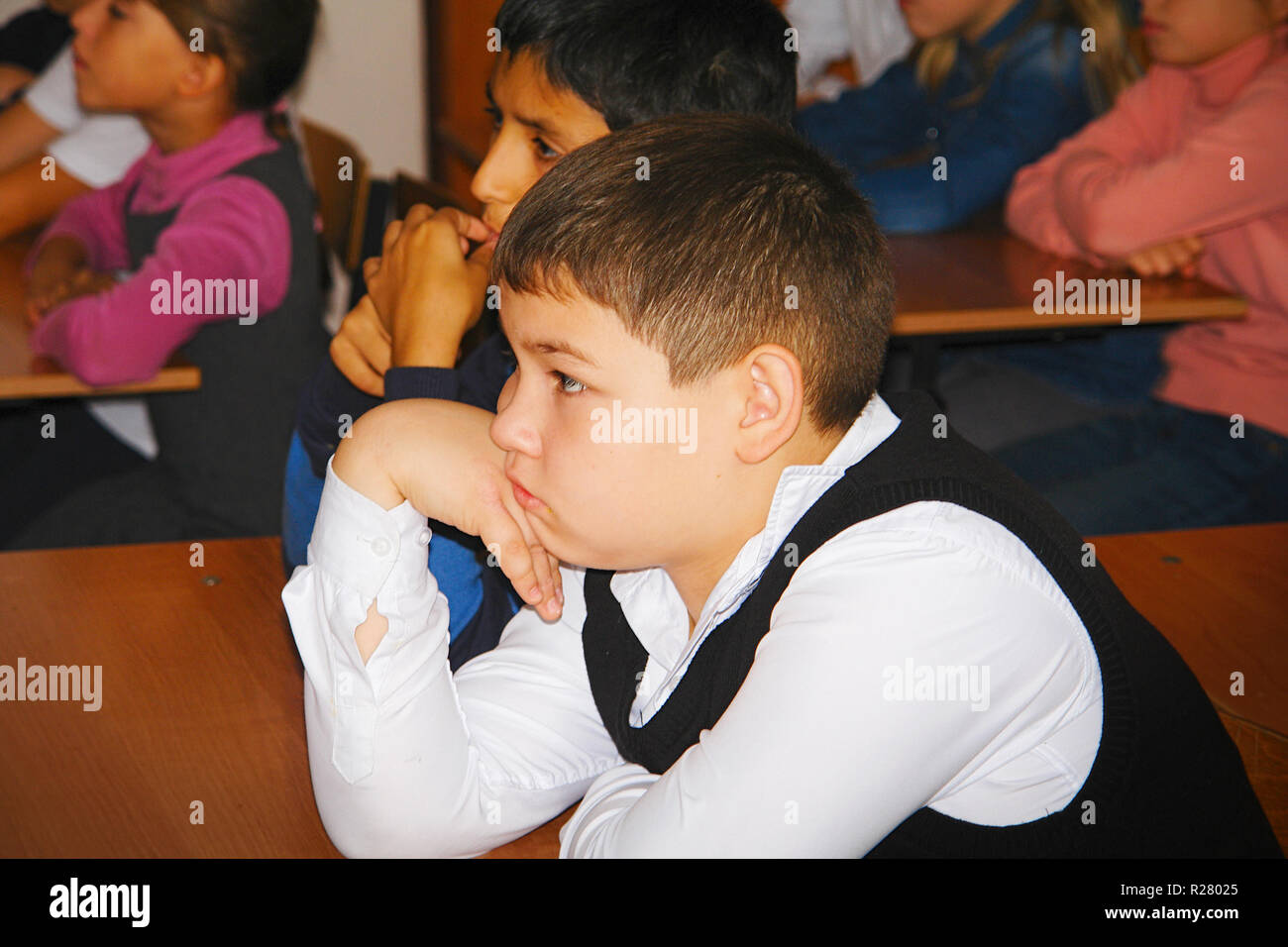 Schoolboy in class listening to the teacher - Stock Image