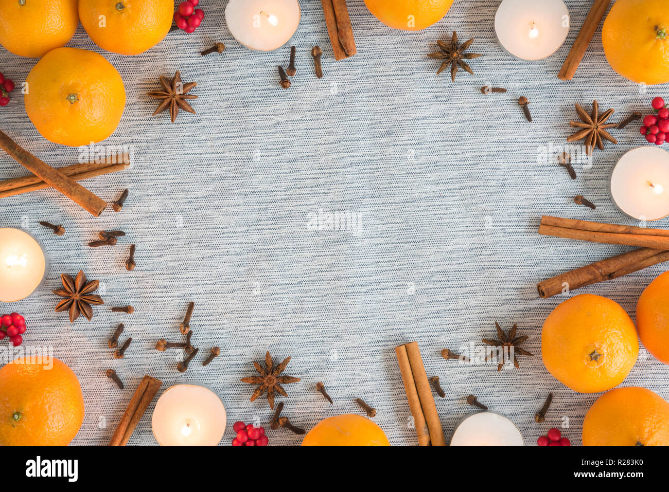 Christmas flat lay frame of oranges, candles, and spices - Stock Image