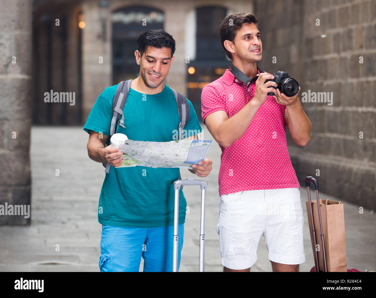 Portrait of two men who are walking with map and photographing on the street in Barcelona. - Stock Image